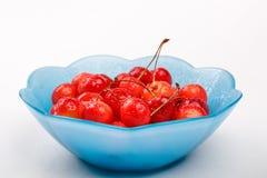 Зрелые ягоды вишни с капельками воды в голубую плиту на белой предпосылке Стоковые Фотографии RF