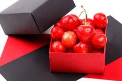 Зрелые ягоды вишни с капельками воды в раскрытую бумажную подарочную коробку на белой предпосылке Стоковое Изображение