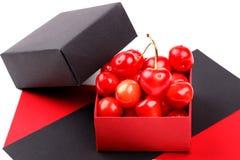 Зрелые ягоды вишни с капельками воды в раскрытую бумажную подарочную коробку на белой предпосылке Стоковая Фотография RF