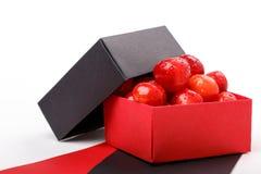 Зрелые ягоды вишни с капельками воды в раскрытую бумажную подарочную коробку на белой предпосылке Стоковые Фото