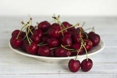 Зрелые ягоды вишни с капельками воды на белой плите на белой деревянной предпосылке Стоковая Фотография