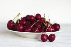 Зрелые ягоды вишни с капельками воды на белой плите на белой деревянной предпосылке Стоковое Изображение RF