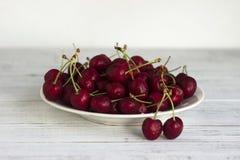 Зрелые ягоды вишни с капельками воды на белой плите на белой деревянной предпосылке Стоковые Фото