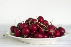 Зрелые ягоды вишни с капельками воды на белой плите на белой деревянной предпосылке Стоковое Изображение