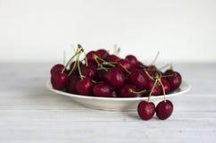 Зрелые ягоды вишни с капельками воды на белой плите на белой деревянной предпосылке Стоковое фото RF
