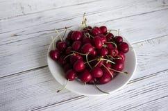 Зрелые ягоды вишни с капельками воды на белой плите на ягодах вишни whRipe с капельками воды на белой плите на whit Стоковое Изображение RF