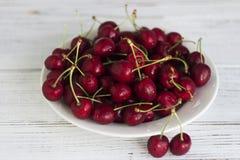 Зрелые ягоды вишни с капельками воды на белой плите на ягодах вишни whRipe с капельками воды на белой плите на whit Стоковые Фотографии RF