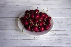 Зрелые ягоды вишни с капельками воды на белой плите на wh Стоковые Фотографии RF