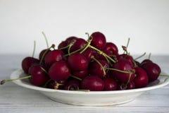 Зрелые ягоды вишни с капельками воды на белой плите на wh Стоковое Фото