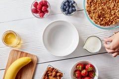 Зрелые ягоды, granola, гайки, мед и пустая плита на белом деревянном столе Рука ` s женщины держит стекло молока Стоковые Изображения RF