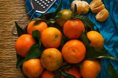Зрелые tangerines с листьями на деревенской таблице с тканью стоковая фотография
