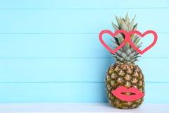 Зрелый ананас с губами и сердцами на голубой предпосылке стоковое фото