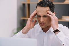 зрелый бизнесмен при тягостная мигрень пробуя работать Стоковая Фотография RF