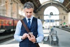 Зрелый бизнесмен с smartphone на вокзале Стоковое Фото