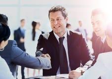 Зрелый бизнесмен тряся руки для того чтобы загерметизировать дело с его партнером и коллегами в современном офисе Стоковые Фотографии RF