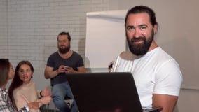 Зрелый бородатый бизнесмен используя ноутбук, его команду дела на пре акции видеоматериалы