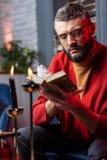 Зрелый бородатый будущий упредитель читая старую маленькую книгу для волшебников стоковая фотография rf
