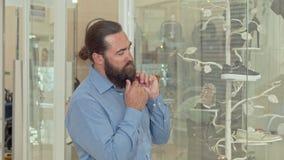 Зрелый бородатый человек смотря внимательно на дисплее магазина одежды акции видеоматериалы