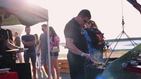 Зрелый высокорослый человек с рыбами картофеля фри солнечных очков на огромном гриле угля для туристов акции видеоматериалы