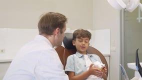 Зрелый дантист усмехаясь к камере пока работающ с прелестным мальчиком сток-видео
