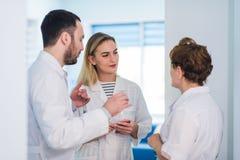 Зрелый доктор обсуждая с медсестрами в больнице прихожей Врачуйте обсуждать терпеливое состояние случая с его медицинским персона Стоковое Изображение
