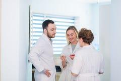 Зрелый доктор обсуждая с медсестрами в больнице прихожей Врачуйте обсуждать терпеливое состояние случая с его медицинским персона Стоковые Изображения
