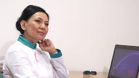Зрелый женский азиатский доктор ослабляя с чашкой кофе на ее офисе после работы стоковое фото rf