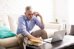 Зрелый испанский человек говоря на телефоне и делая примечания Стоковое Изображение RF