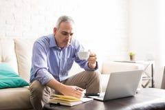 Зрелый испанский человек работая от дома Стоковое фото RF