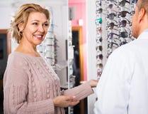 зрелый клиент optician человека консультируя зрелая блондинка около солнечных очков дисплея Стоковые Фотографии RF