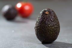 Зрелый конец авокадоа вверх на серой конкретной предпосылке, здоровой еде Стоковое Фото