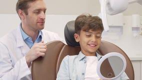 Зрелый мужской дантист работая с очаровывать молодой мальчика видеоматериал