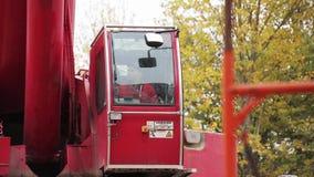 Зрелый мужчина в красных форме и крышке сидит в красной кабине крана и приводится в действие ее акции видеоматериалы
