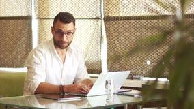 Зрелый привлекательный голубоглазый работник офиса смотрит в рамку и улыбки широко Человек носит белую рубашку сток-видео