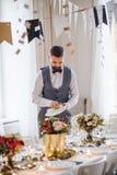 Зрелый человек внутри помещения в наборе комнаты для партии, полируя плит стоковые изображения