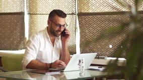Зрелый человек в белой рубашке с бородой говоря по телефону пока сидящ на ноутбуке Смех весело, висит вверх и видеоматериал