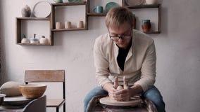 Зрелый человек в стеклах сидящ и держащ глина на колесе для формировать будущее pott сток-видео