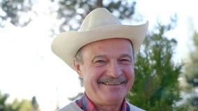 Зрелый человек в усмехаться шляпы, делая в порядке знак с рукой видеоматериал