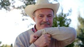 Зрелый человек в усмехаться шляпы, делая в порядке знак с рукой акции видеоматериалы