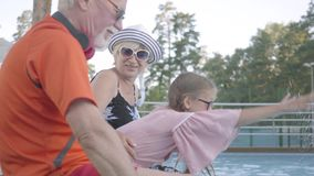 Зрелый человек, женщина и маленькая девочка сидя на краю бассейна Милая девушка брызгая воду с руками Бабушка сток-видео