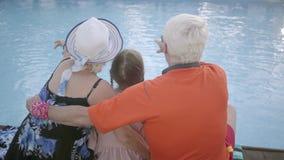 Зрелый человек, женщина и маленькая девочка сидя на краю бассейна, задний взгляд Бабушка, дед, и внук акции видеоматериалы