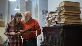 Зрелый человек приглашает внучку прочитать книгу совместно сток-видео