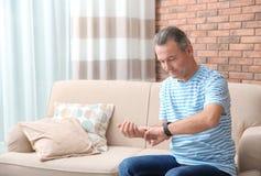 Зрелый человек проверяя ИМП ульс с пальцами внутри дома стоковая фотография
