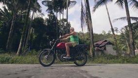 Зрелый человек путешествуя на мотоцикле на дороге деревни на тропическом ландшафте пальм Мотоцикл катания старшего человека дальш акции видеоматериалы