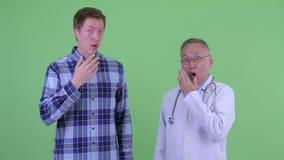 Зрелый японский доктор человека с молодым человеком смотря сотрясенный совместно акции видеоматериалы