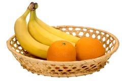 3 зрелых банана и 2 апельсина в плетеной плите Стоковые Изображения RF