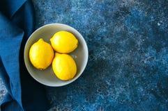 3 зрелых желтых лимона в сером шаре на backgrou голубого камня Стоковое фото RF