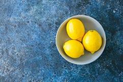 3 зрелых желтых лимона в сером шаре на nackgrou голубого камня Стоковые Фото