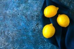 3 зрелых желтых лимона на предпосылке голубого камня Взгляд сверху Стоковое Изображение RF
