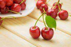 2 зрелых красных вишни с зеленым концом лист на фоне белой плиты с пуком вишен Стоковые Изображения